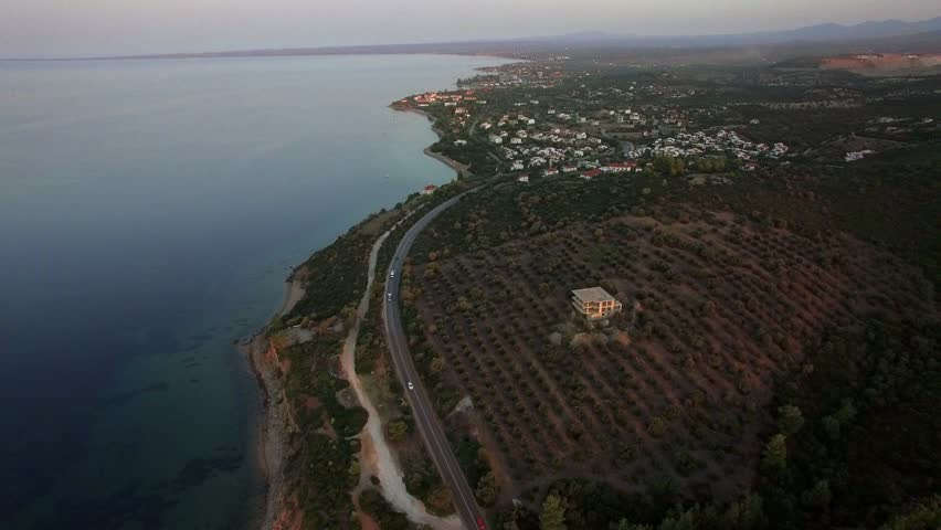 Aerial shot of Trikorfo Beach shoreline, Greece. View to the quiet sea, cottages on the shore and road along the waterfront running through the green areas | Shutterstock HD Video #1018921111