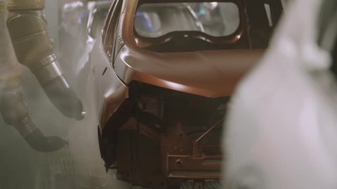 Slow motion painting department inside a car factory. Automotive industry