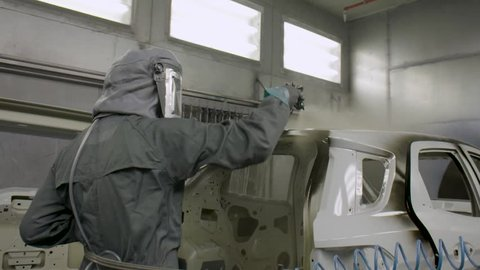 Slow motion painting department inside a car factory. Automotive industry. Factory working wearing protective gear spray painting the car carcass