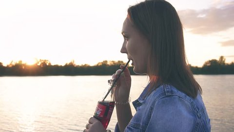 girl drinking from a straw coca-cola lemonade at sunset in nature