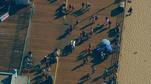 Aerial view of people walking on Santa Monica Pier shoreline on a sunny day in Los Angeles, California. Shot on 4K RED camera.