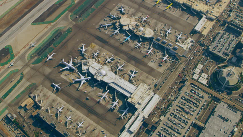 Aerial view of airplanes at terminals at LAX runway on a sunny day in Los Angeles, California. Shot on 4K RED camera.