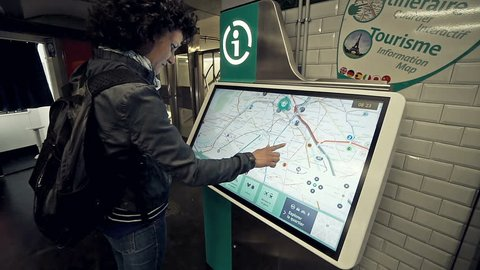 Paris, France - May 06, 2017: Traveler woman find the best route on interactive info touch screen map at metro station in Paris. Bying rail tickets from a vending machine at a city center subway stati