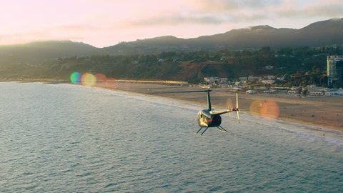 Aerial view of helicopter flying over beach cliff houses during beautiful sunset in Los Angeles, California. Wide long shot on 4K RED camera.