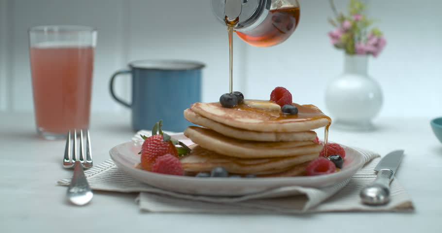 Maple syrup is poured over a stack of pancakes with fruit and butter on a table with a background in soft focus, in slow motion, in soft light. Closeup shot in 4K on a Phantom Flex | Shutterstock HD Video #1019032651