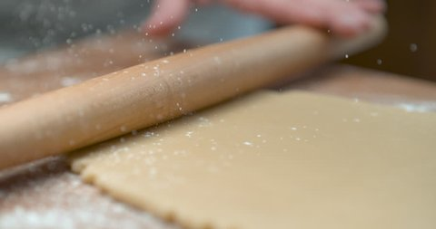 Sprinkled flour drops onto dough being rolled with a rolling pin by a pastry chef. Closeup shot 4K Phantom Flex. Chef's Table, Food Network and cooking show inspired footage.