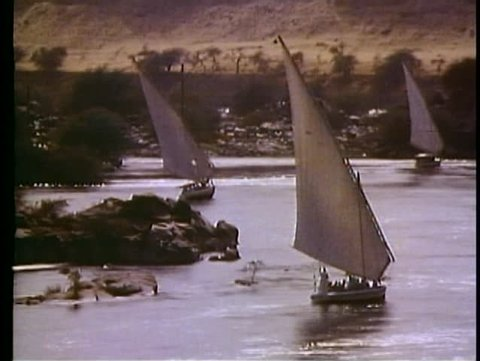 ASWAN, EGYPT, 1977, The Nile River, feluccas, sailboats, three boats, backlit