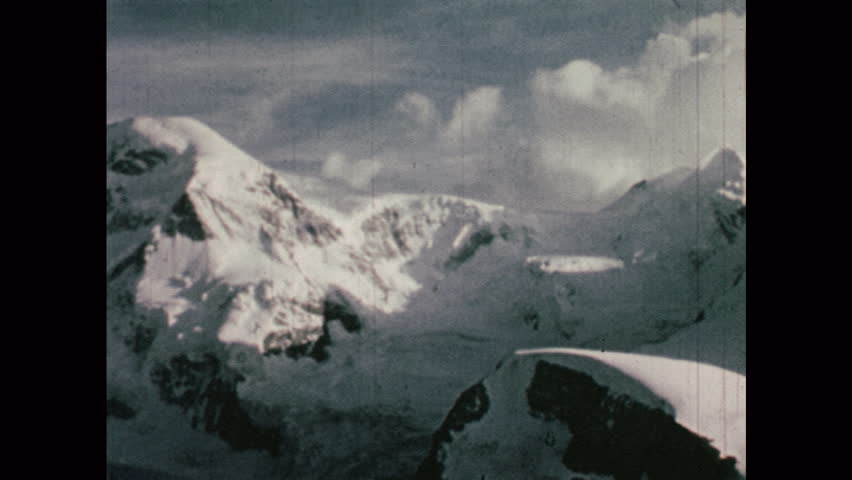 1950s: EUROPE: SWITZERLAND: hotel and chapel at start of mountain ascent. View across mountains. Snow covered mountains | Shutterstock HD Video #1019070061