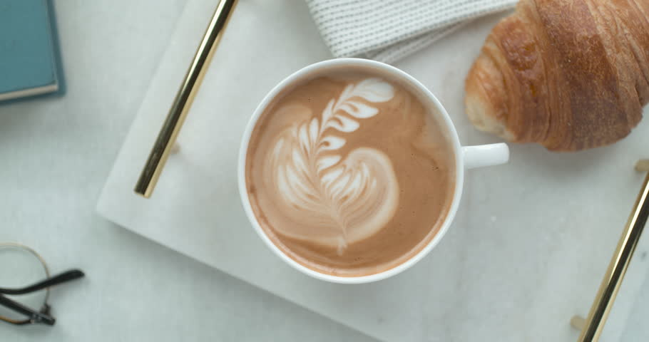 Pretty latte leaf design in white cup next to butter croissant and reading glasses ultra slow motion closeup with 4k Phantom Flex camera.