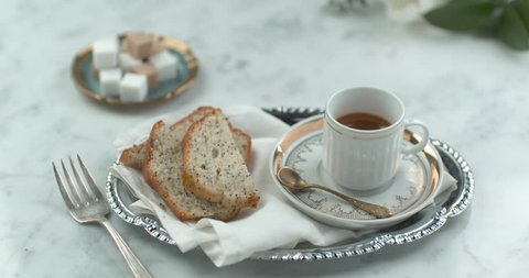 Fancy English tea and cake served on silverware in ultra slow motion closeup with 4k Phantom Flex camera