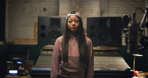 Portrait of urban girl with long hair and backwards baseball cap in pink hoodie and jeans in front of professional mixing board in a recording studio. Medium shot on 4K RED camera.