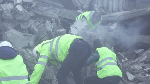 a group of rescue workers dismantle the rubble of the destroyed building after the earthquake close up