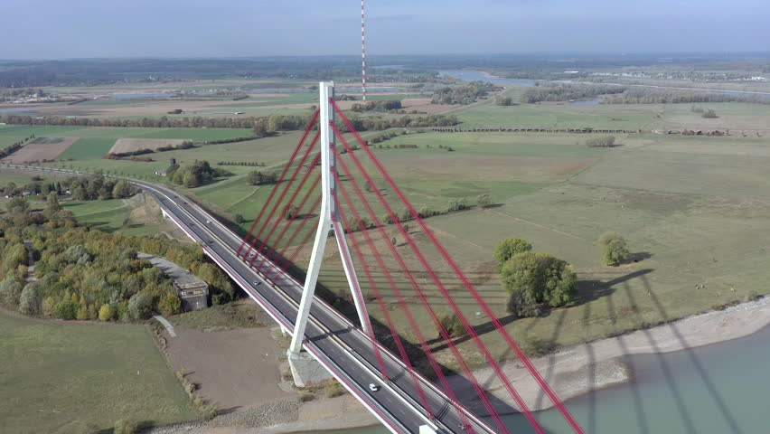 Vehicles Crossing a Huge Red Cable Stayed Suspension Road Bridge Spanning the River Rhine in Germany