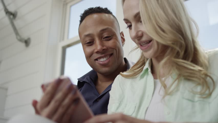 A young interracial couple laugh and hang out as she looks at her smartphone as he looks over her shoulder. | Shutterstock HD Video #1019151511