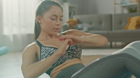 Slow Motion Close Up Shot of a Beautiful Confident Busty Fitness Woman in an Athletic Top is Doing Abdominal Exercises in Her Bright and Spacious Living Room with Modern Interior.