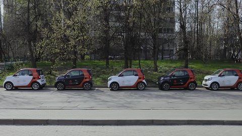 MOSCOW - OCT 13, 2017: Car drive by street near parked electric vehicles of carsharing company You Drive. Slow motion. Car sharing is rental service. Client can return car at any point in town.