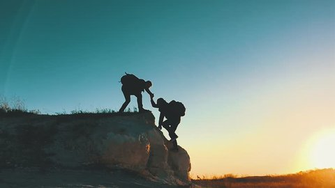 Silhouette of helping hand between two climber. two hikers on top of the mountain, a man helps a man to climb a sheer stone. couple hiking help each other silhouette in mountains with sunlight.