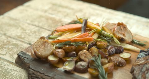Olive oil being poured on roasted potatoes, onions and carrots, with salt sprinkled on roasted rack of pork and thyme on a wood board . Medium shot in slow motion in 4K on a Phantom Flex camera.