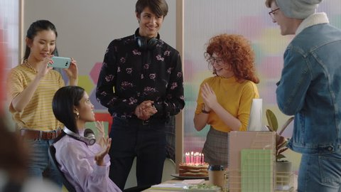 young business people celebrating birthday party happy mixed race woman blowing candles enjoying surprise friends cheering together in colorful office celebration