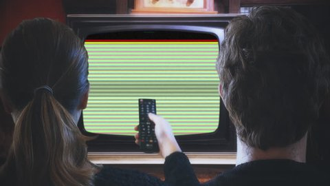 Couple Watching TV Remote Control Green Screen Channels. Couple with TV remote changing channels in a vintage style technology. Old Television green screen