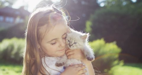 Close up of the small pretty girl standing in the park and hugging cute little fluffy cat. Portrait. Outside.