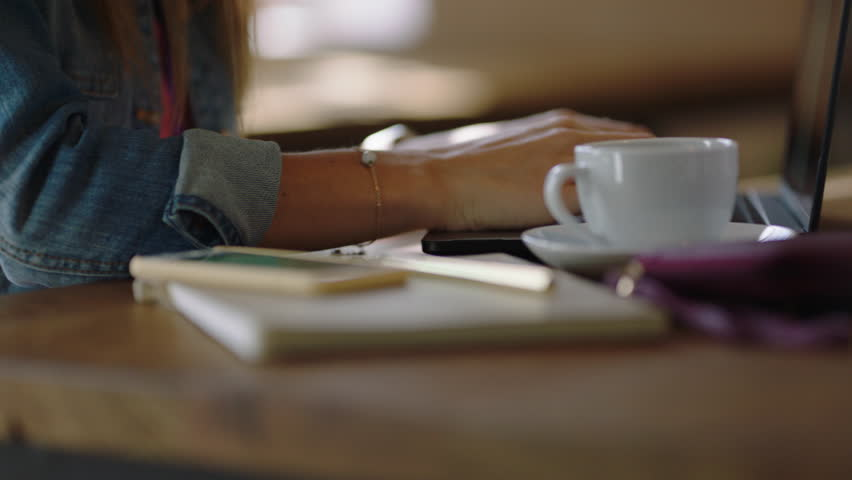close up hands business woman using laptop computer in cafe drinking coffee typing email messages working sharing networking ideas enjoying online social media communication
