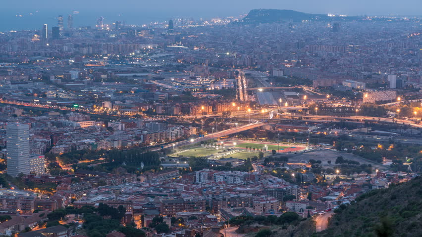 Barcelona and Badalona skyline with roofs of houses and sea on the horizon day to night transition timelapse after sunset. Aerial view from Iberic Puig Castellar Village viewpoint on top of hill | Shutterstock HD Video #1019263711
