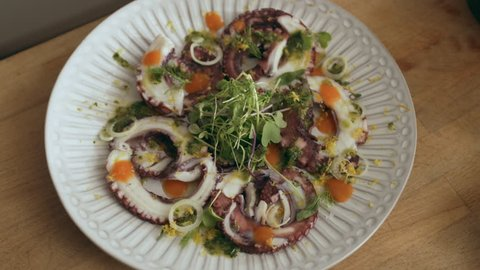 Beautifully plated octopus carpaccio dish on a cutting board. Close shot on a RED camera.