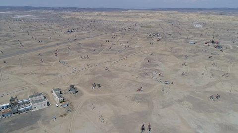 Aerial view of oil field operation and pipeline in Xinjiang desert. Drone view of oil extraction hoe machine pumping unit. Oil and energy industry, oil pump jack land in Northwest China's Xinjiang.