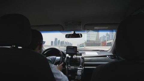 Dubai, UAE - May 15, 2018: Taxi driver in Dubai in a summer day. View from the salon car.