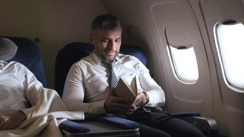 PAN shot of businesspeople relaxing on plane: man giving travel pillow and blanket to unrecognizable female flight attendant as another male passenger reading bookPAN shot of businesspeople relaxing o