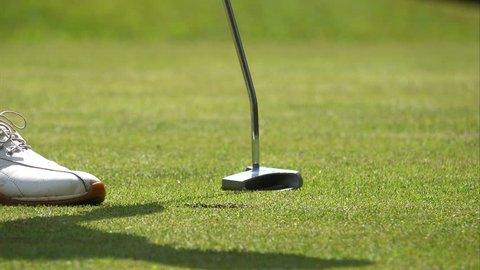 Golf sport concept, Golfer putting golf ball into hole to the winner in open tournament on hills, flag sitting on hole of green, Player walking and picking ball in hole to play continue, the best shot