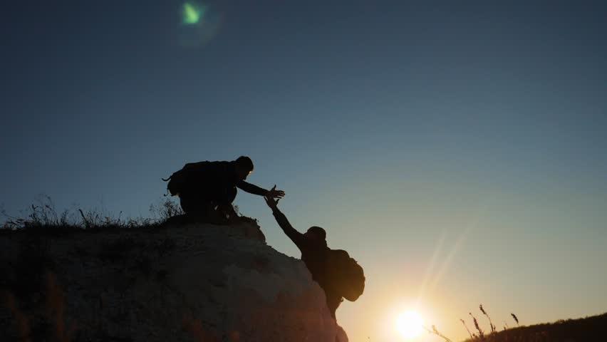 Silhouette two men teamwork tourists climber climbs a mountain. walking tourist hiking adventure climbers sunset climb the mountain . slow motion video. hiker sunlight on top win victory the hill | Shutterstock HD Video #1019465641