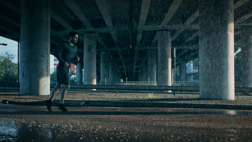 Athletic Muscular Young Man in Sports Outfit is Jogging in the Street on a Rainy Day. He is Running in an Urban Environment Under a Brindge.