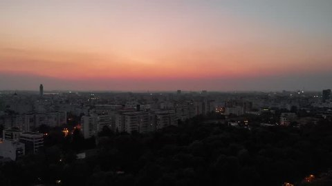 Aerial drone shot of Bucharest Romania buildings at dusk sunset night city streets