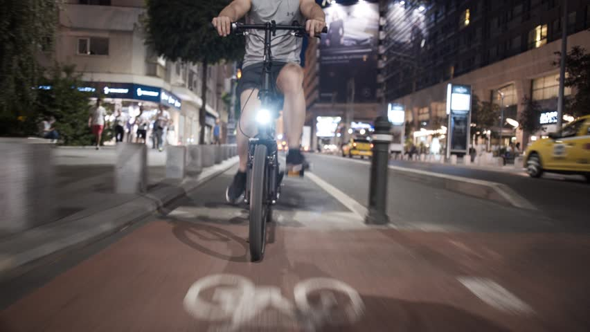 Tracking shot young man biking riding a bike on a city street lights at night in Bucharest  | Shutterstock HD Video #1019496181
