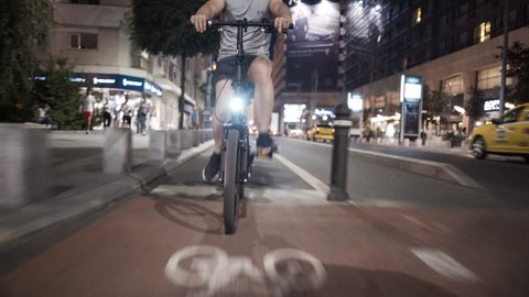 Tracking shot young man biking riding a bike on a city street lights at night in Bucharest