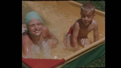 Little boy and girl play in kiddie pool 1956 Close Up