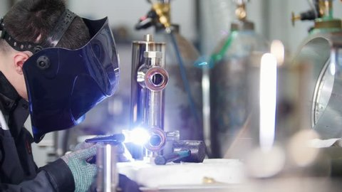 Micro welding. Worker in mask use electro spark engraving equipment for carbide metal at factory.