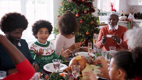 Christmas Crackers Hat.Mixed Race Multi Generation Family Sitting At Their Christmas Dinner Table Reading Jokes And Putting On Paper Party Hats From Christmas Crackers Close Up