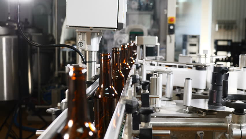 Technological line in brewery. Empty glass bottles on conveyor being transported. Technological process of beer production. 4k #1019546401