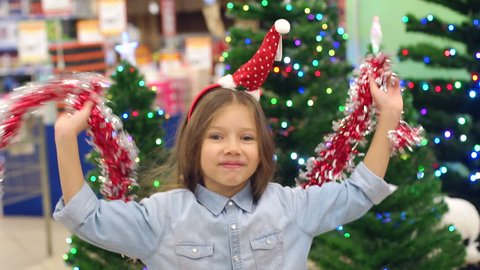 A little funny girl in the supermarket plays and dances with garlands on the background of decorated Christmas trees with flashing lights, she has a Hoop with a Santa hat on her head. Slow motion.
