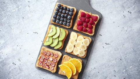 Healthy breakfast toasts. Wholegrain bread slices with peanut butter and various fruits. Served on grey cutting board. Top view, grey stone background. Dieting concept