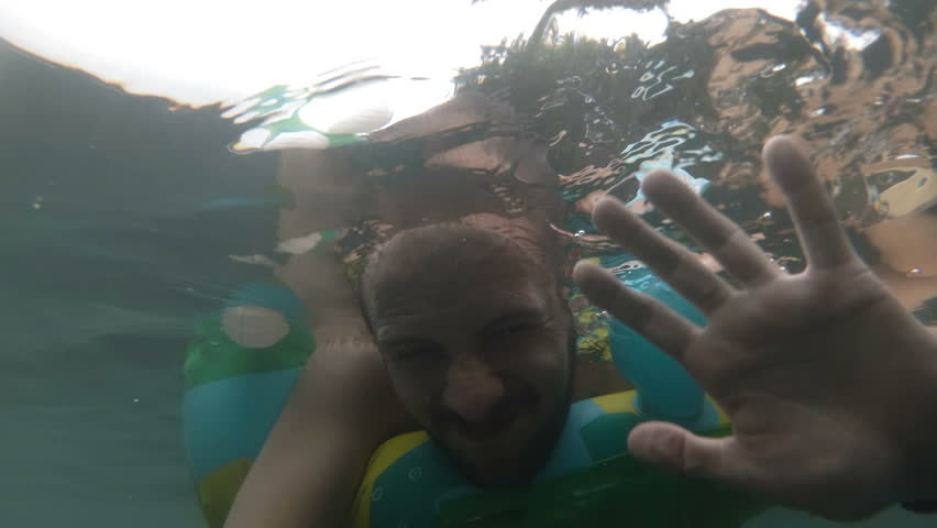 Underwater portrait of smiling man. Person having fun in swimming pool. Summer vacation concept. selphi. #1019667451