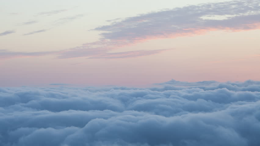 High altitude time lapse of light pink wispy sunset clouds in a colorful pastel pink and yellow sunset sky above a carpet of rolling puffy blue inversion clouds isolated in the sky
