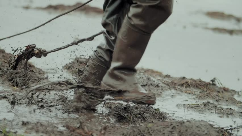Man walks through the mud in rubber boots