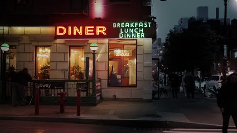 NEW YORK CITY - Circa 2018 - A nighttime exterior establishing shot of a city corner diner in midtown Manhattan as traffic and pedestrians pass nearby. Day/night matching available.