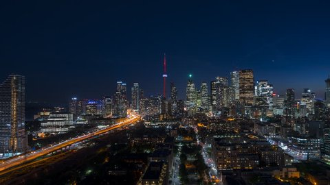 The historic and modern Toronto architecture buildings with cars commuting and long exposure light streaks depict fast movement in a quick paced urban environment.