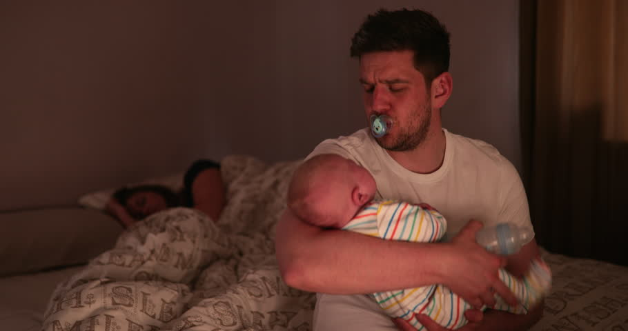 Dad checking on his newborn son, during the night, while his wife is fast asleep behind his on the same bed that he is sitting on to check his newborn. | Shutterstock HD Video #1019883121