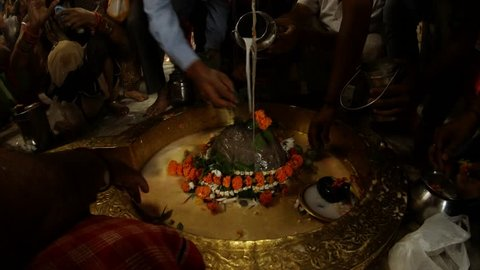Hands of big crowd of people pour water and milk over swayambhu self-existing lingam and put leaves and flowers in ancient hindu temple Rishikesh